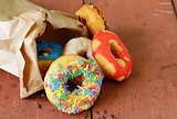 donuts with colorful glaze on the wooden background