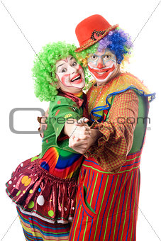 A couple of smiling clowns dancing
