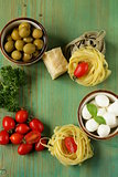 Italian still life - olives, mozzarella cheese, pasta, tomatoes
