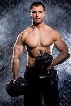 Powerful guy with a dumbbells