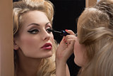 aristocratic girl applying mascara on mirror