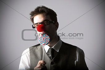 Funny portrait of young stylish man with clown nose eating lolli