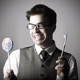 Happy smart young man with a lollipop in one hand and a toothbru