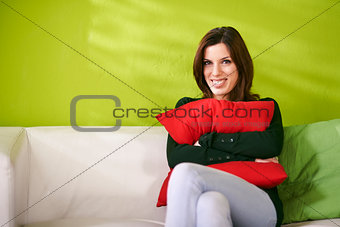 portrait of happy woman holding pillow and smiling