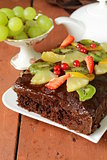 chocolate brownie cake decorated with different fruits