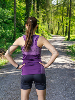 Runner looking at the path through the forest