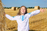 small rural girl on harvest field with straw bales