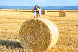 small rural girl on the straw after harvest field with straw bal