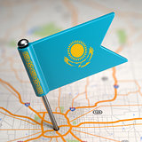 Kazakhstan Small Flag on a Map Background.