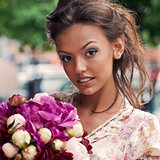 a beautiful young girl in summer dress with a bunch of flowers i
