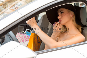 elegant blond with lipstick in car