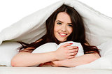 Woman laid in bed smiling