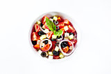 Light salad with vegetables and basil. On white.