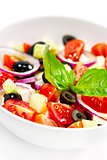 Tasty greek salad with bright vegetables, garnished with basil.