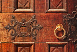 Closeup of old ornate wooden door with a gold door handle in Alba, Italy.