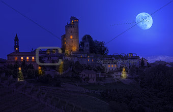 Small town on the hill under the sky with full moon at night in Piedmont, Northern Italy.