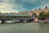 Train passing on famous Pont de Bir-Hakeim bridge across Seine River in Paris, France (toned).