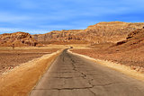Paved road through Arava desert among red mountains in Timna national park, Israel.
