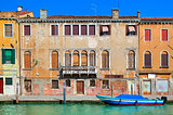 Typical old colorful brick house, wooden shutters on windows and small canal in Venice, Italy.