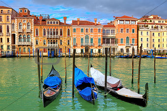 Gondolas on Grand Canal in front of old colorful houses in Venice, Italy.