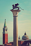 Bronze sculpture of winged lion on column as San Giorgio Maggiore church on background in Venice, Italy (toned, vertical composition).