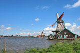 Wooden windmills along river under beautiful blue sky with white clouds in typical dutch village of Zaanse Schans.
