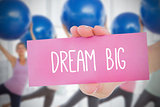 Woman holding card saying dream big