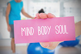 Woman holding pink card saying mind body soul