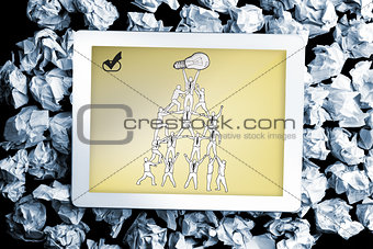 Composite image of team holding up light bulb