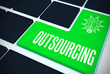 Outsourcing on black keyboard with green key