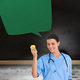 Composite image of happy surgeon holding an apple with speech bubble