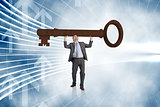 Composite image of businessman carrying large key with arms raised