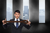 Composite image of unsmiling businessman carrying large key