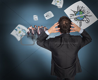 Composite image of stressed businessman with hands on head with tiny businessmen