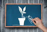 Composite image of hand drawing plant with chalk