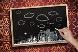 Composite image of hand drawing cityscape with chalk