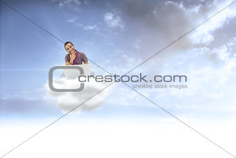 Composite image of thinking man sitting on floor using laptop and smiling