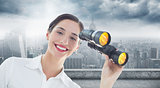 Composite image of smiling businesswoman with binoculars