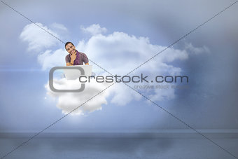Composite image of thinking man sitting on cloud  using laptop and smiling