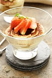 Italian dessert tiramisu decorated with strawberries in a glass beaker
