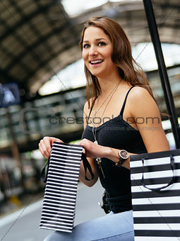 Waiting at the train station with her shopping bags