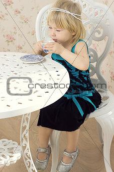 Little girl in a beautiful dress drinks tea