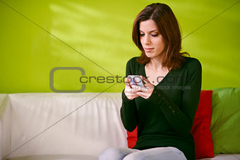 portrait of girl reading sms on smarthphone at home