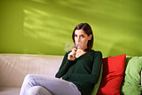 young woman smoking electronic cigarette at home