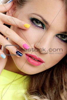 Beautiful girl touch her face with colored fingers