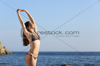 Beautiful fitness woman body wearing a swimsuit on the beach