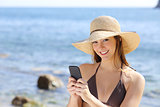 Beautiful happy woman texting on a smart phone on the beach
