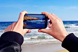 someone taking a picture of a beach with a smartphone