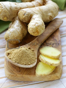 ground ginger in a wooden spoon, fresh root in the background