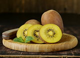 ripe yellow kiwi on a wooden board